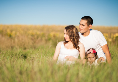 Photo of a happy family sitting in a grassy field posing for the camera