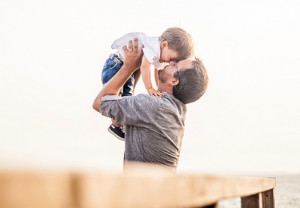 Photo of a man holding his child in the air