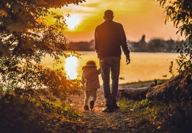 Photo of a man walking with a child while looking at a sunset