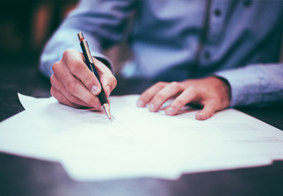 Photo of a man writing on a piece of paper with a black pen