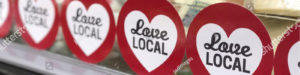 """Photo of a red circle with the text of """"Love Local"""" in a white heart"""